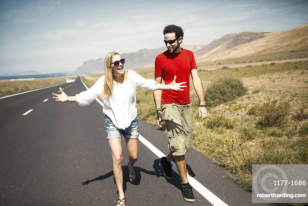 Full length of happy woman talking with man while walking on road
