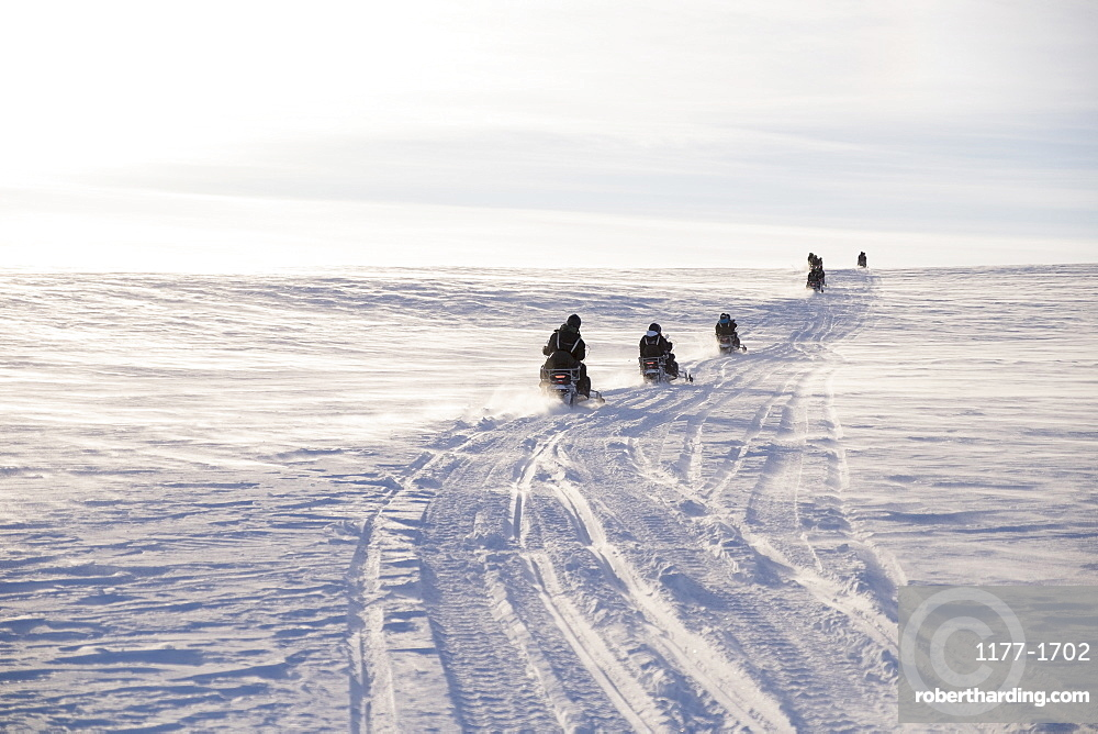 People driving snowmobiles on field against sky during winter