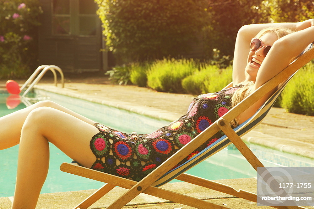 Side view portrait of cheerful woman relaxing on deck chair at poolside