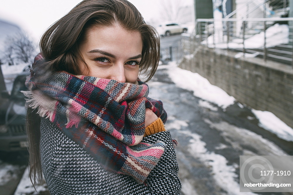 Portrait confident young woman in plaid scarf on snowy winter street