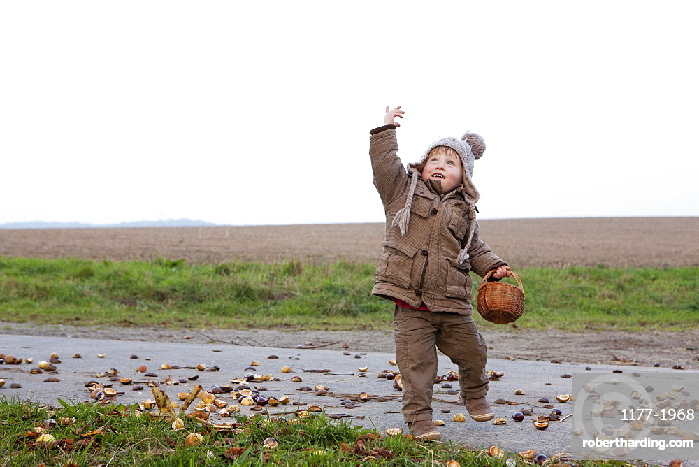 Playful girl with basket on rural road