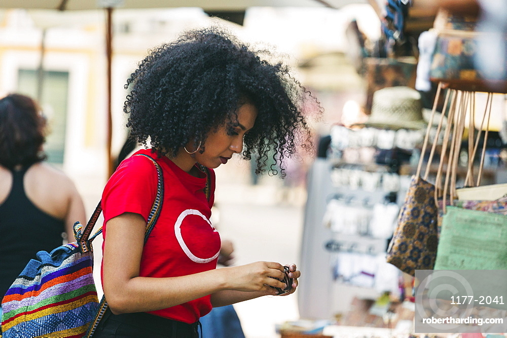 Young woman shopping for jewelry at market stall