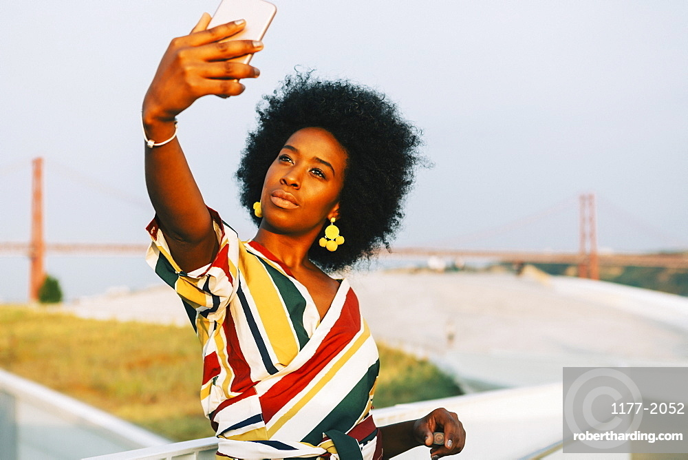 Confident young woman taking selfie with 25 de Abril Bridge in background, Lisbon, Portugal