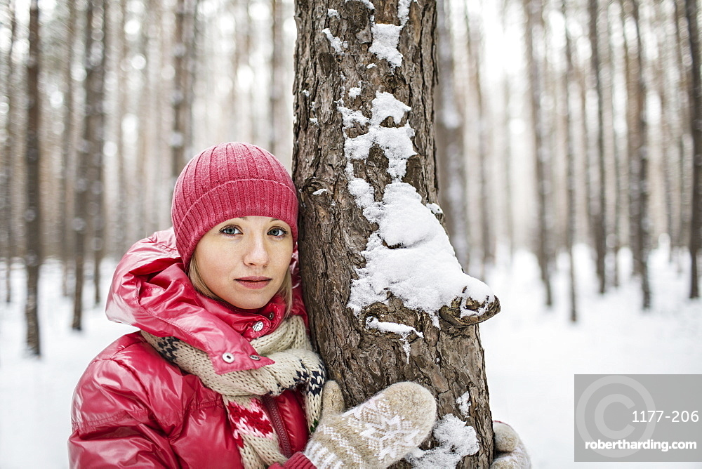 A woman wearing warm clothing posing next to a tree in winter