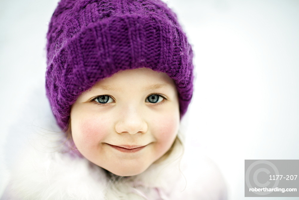 A young smiling girl wearing a knit cap, outdoors in winter