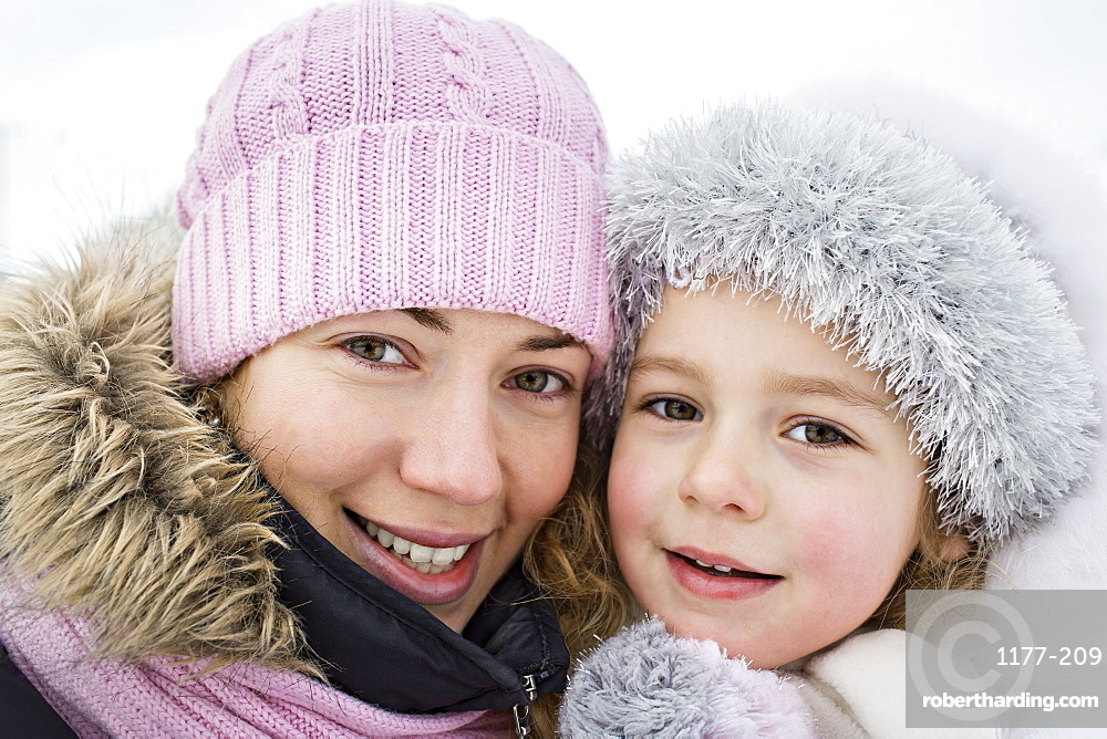 A cheerful mother and daughter in warm clothing outdoors in winter