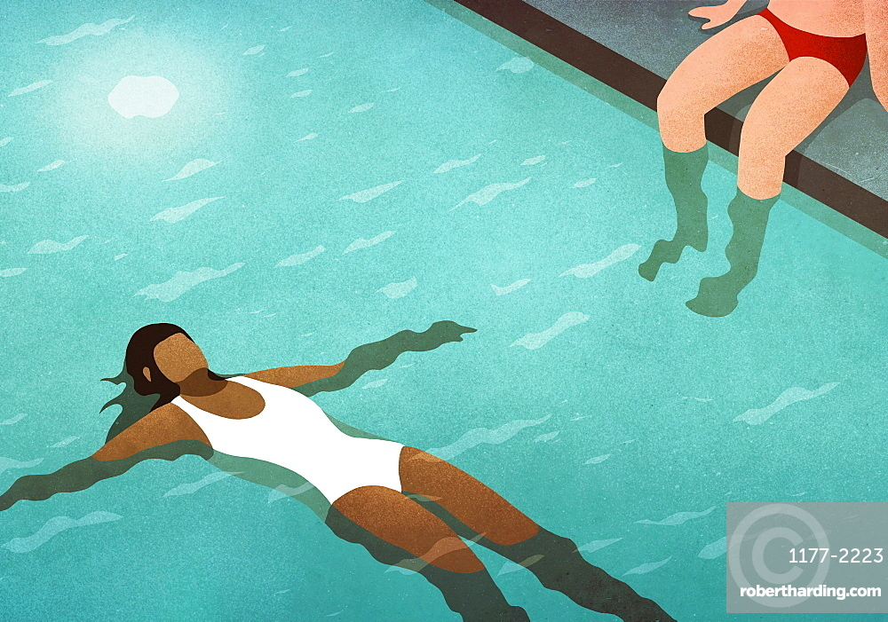 Serene woman floating on back in swimming pool