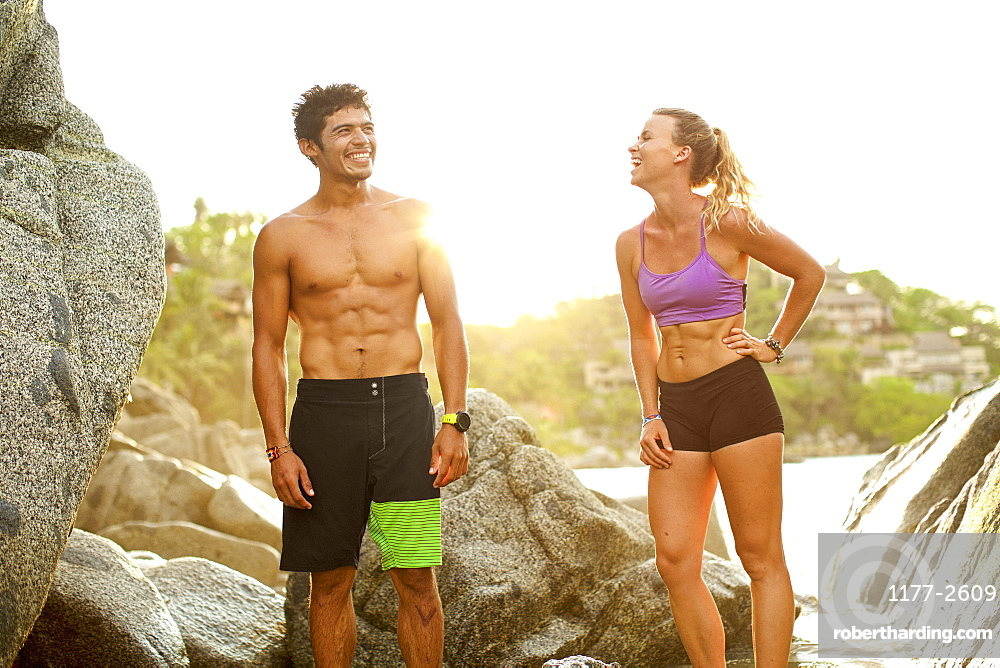 Young, fit couple laughing on beach, Sayulita, Nayarit, Mexico