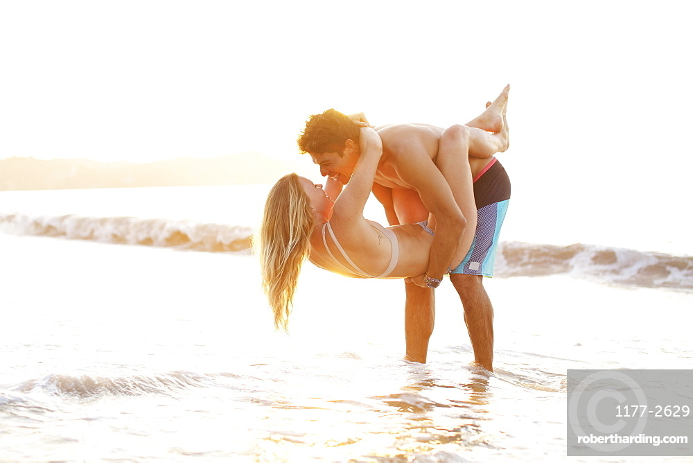 Playful, affectionate young couple wading in ocean