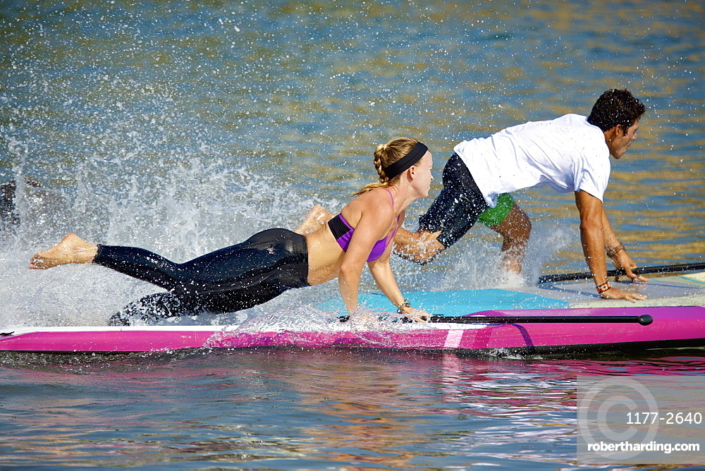Young couple riding paddleboard on sunny ocean