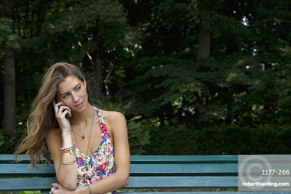 Young woman sitting on park bench using mobile phone