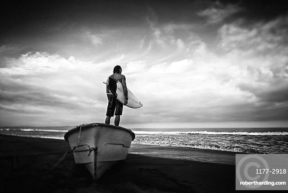 Male surfer with surfboard standing on beached boat, Higuera Blanca, Nayarit, Mexico