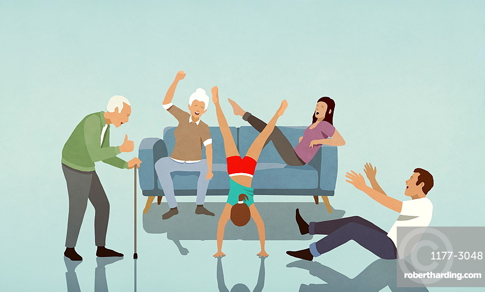 Happy multi-generation family cheering for girl doing handstand in living room