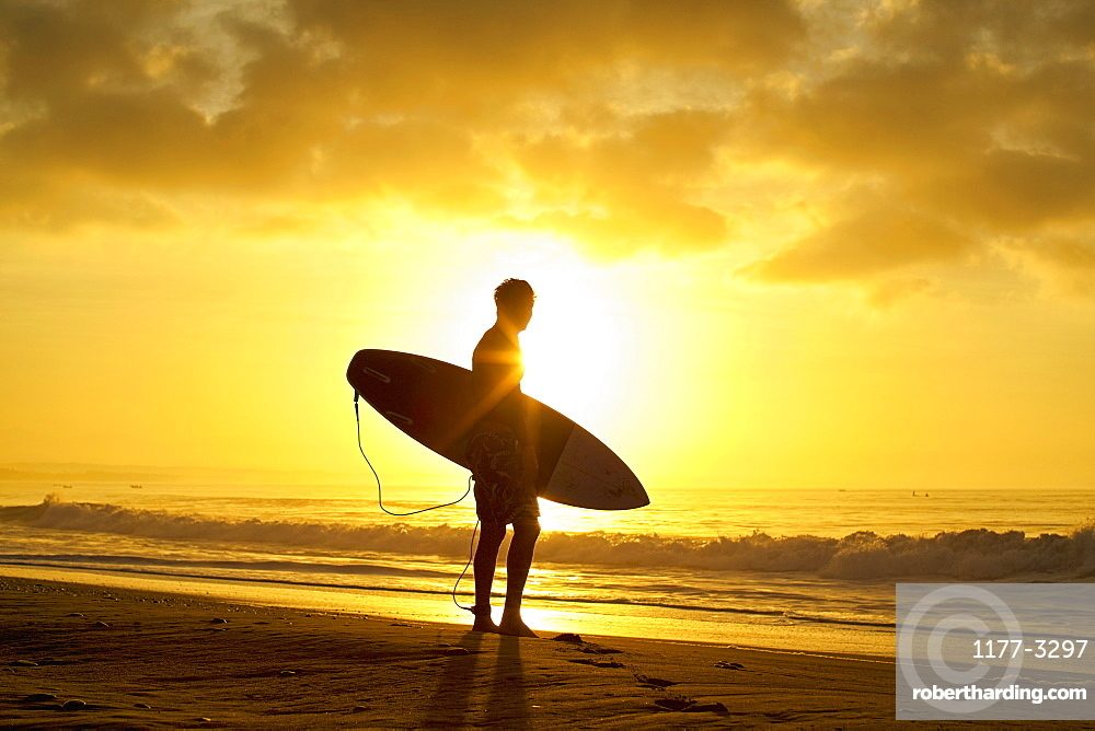 Silhouetted male surfer with surfboard on tranquil, sunset ocean beach
