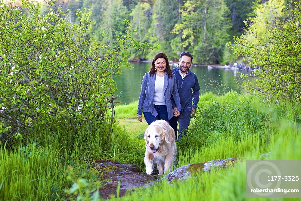 Happy couple with dog hiking along lush green lakeside, Mill Bay, British Columbia, Canada