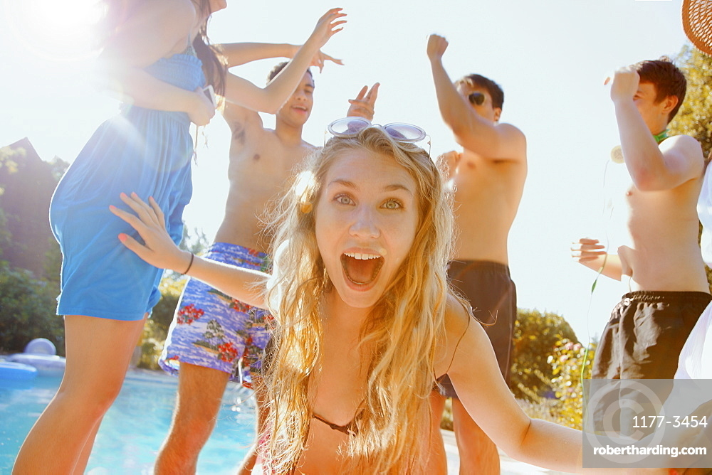 Portrait exuberant teenage girl dancing with friends at sunny summer poolside