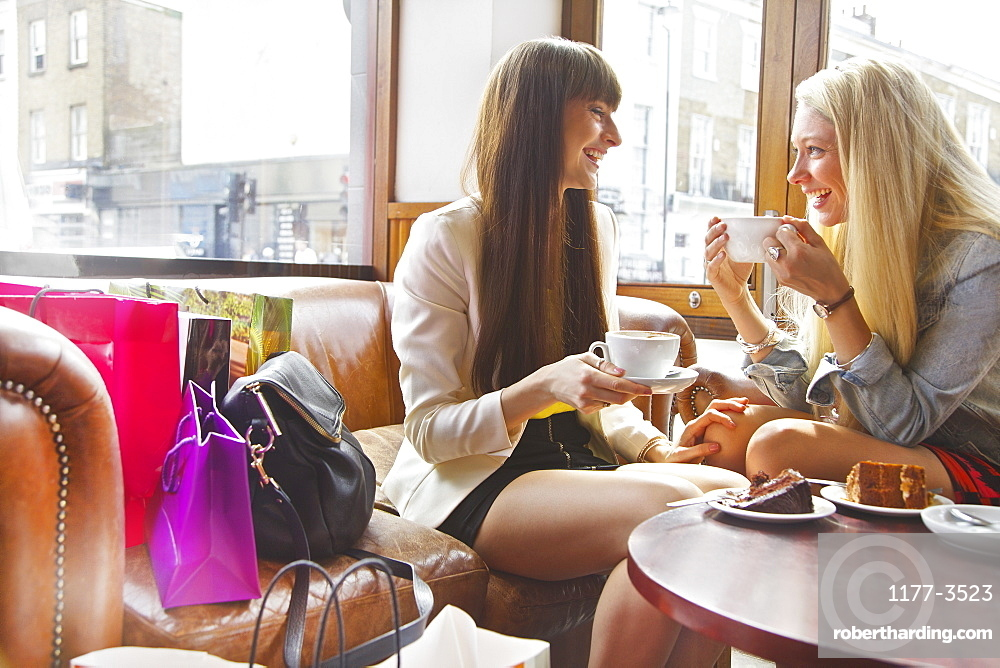 Young women friends with shopping bags enjoying coffee and dessert in cafe