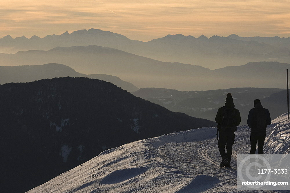 Silhouetted people hiking on snowy mountain, Brixen, South Tyrol, Italy