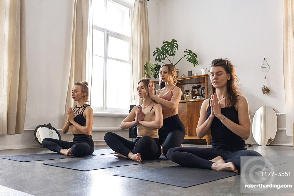 Yoga instructor and students meditating in lotus position in yoga class