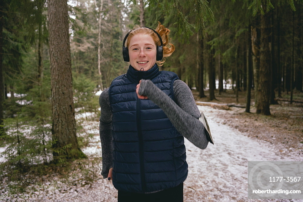 Portrait confident woman running in snowy woods