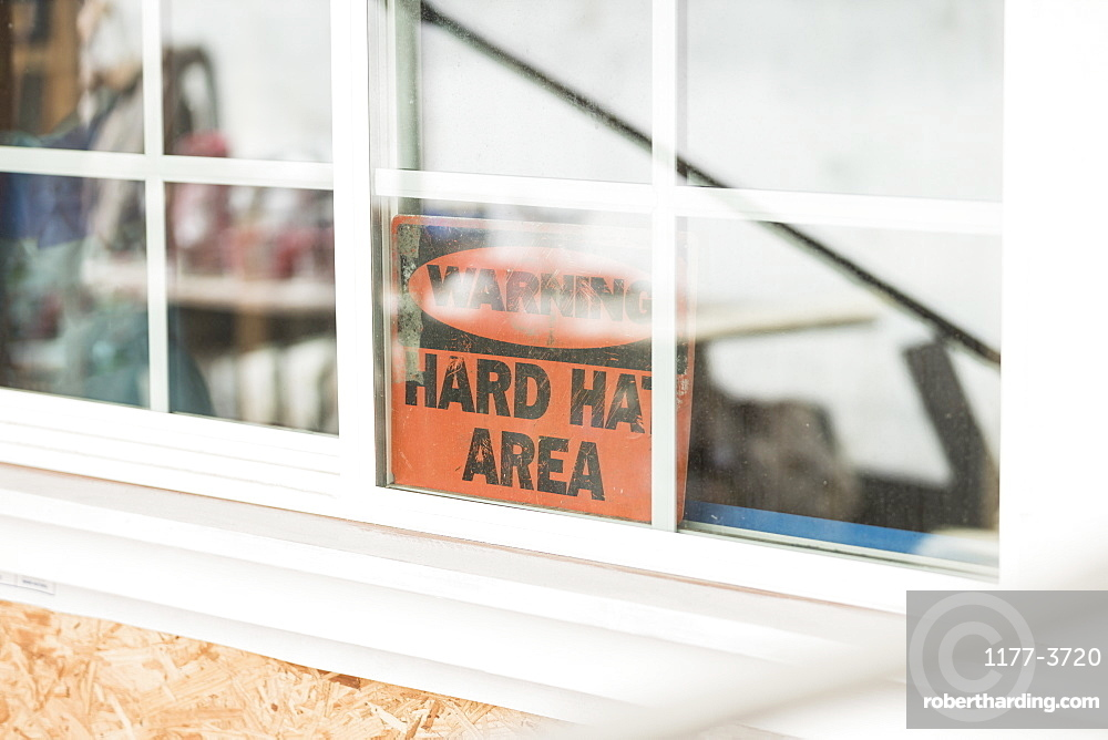 Hard hat warning sign in window at construction site