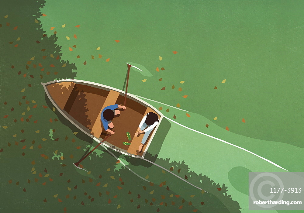 Autumn leaves falling around couple in rowboat on lake