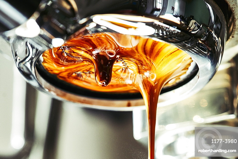 Close up espresso dripping from stainless steel portafilter