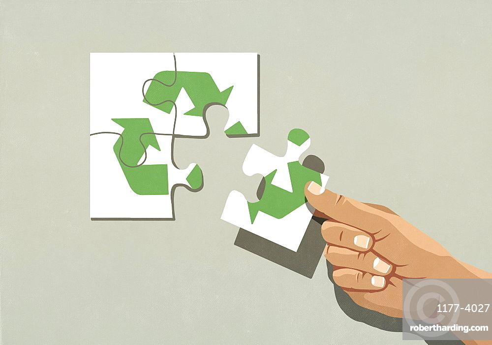 Hand finishing recycling symbol jigsaw puzzle with missing piece