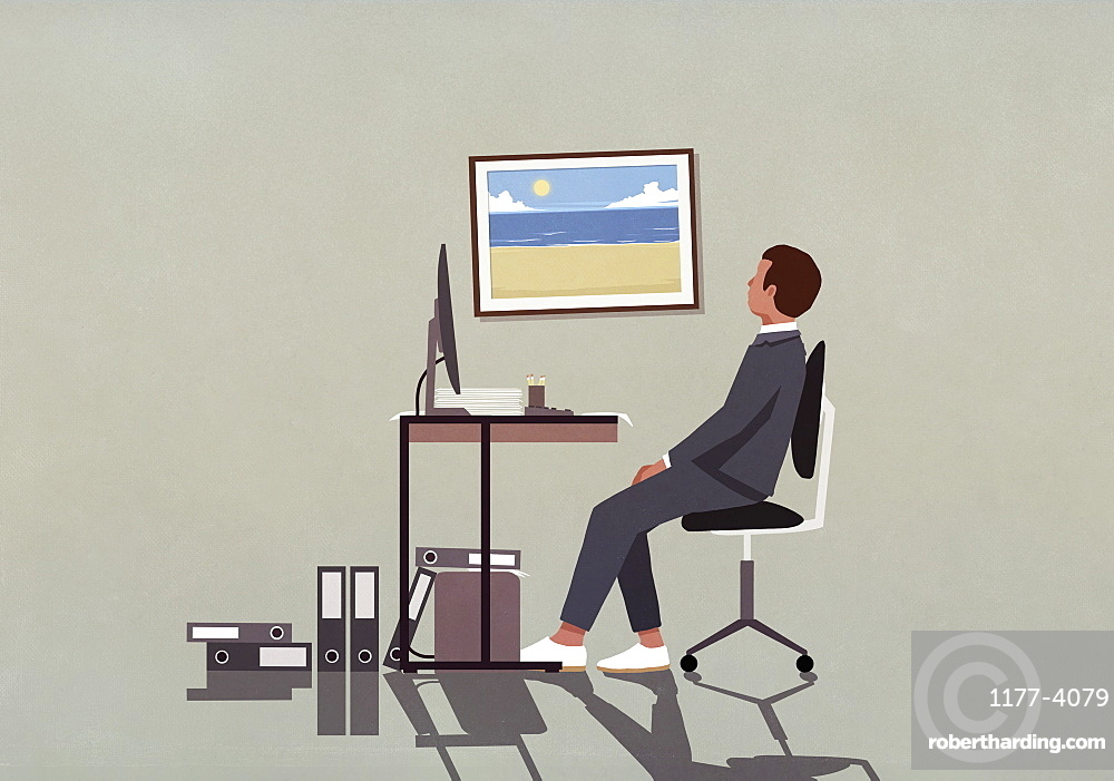 Businessman at office desk looking at photograph of beach on wall
