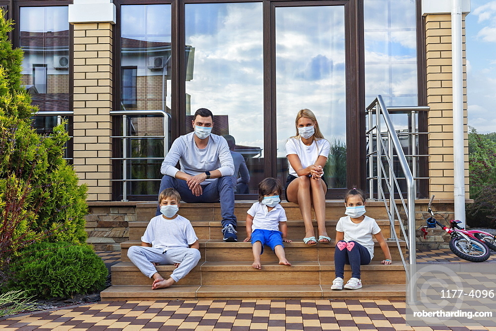 Portrait family in face masks on patio steps of house
