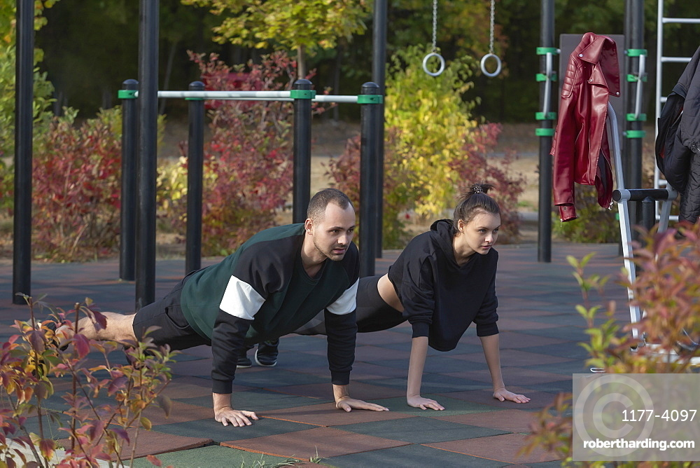 Athletic young couple doing plank exercises at park playground