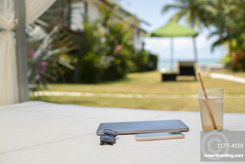 Coconut water, sunglasses, smart phone and notebook on cabana bed
