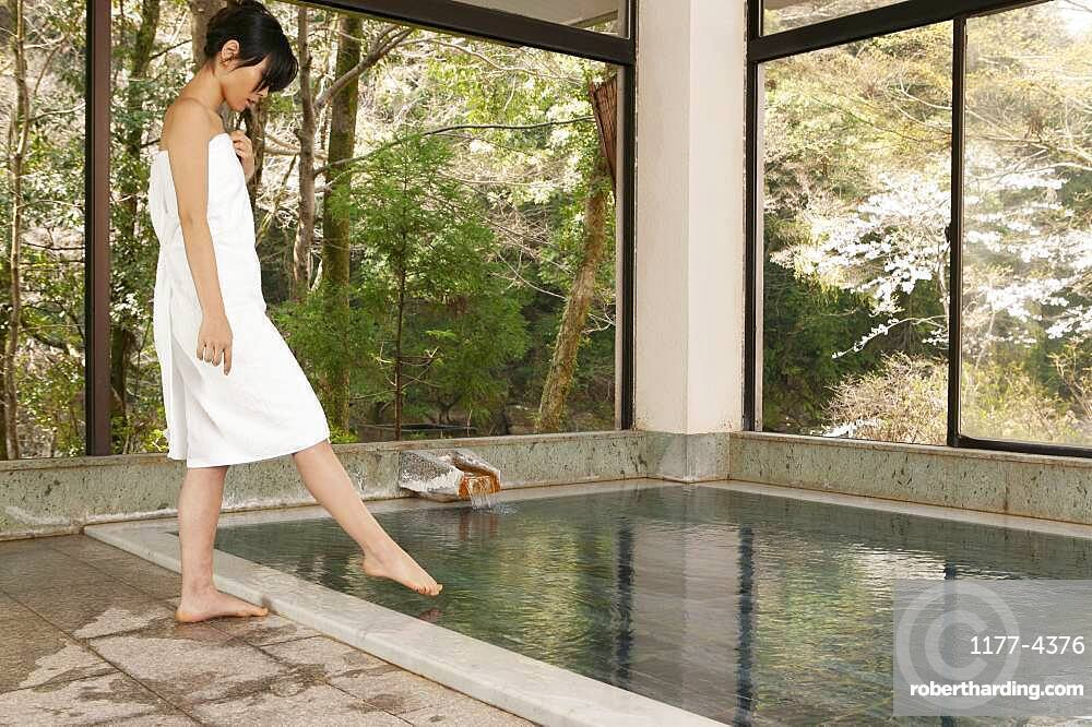 Young woman in towel dipping toe in water at Onsen
