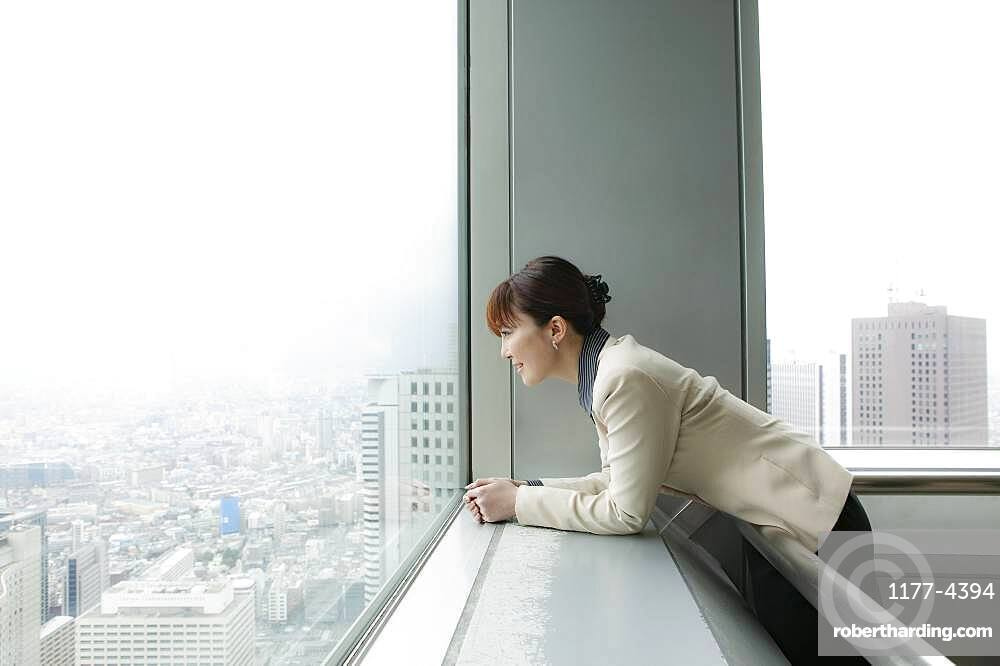 Businesswoman looking out at city view from highrise office