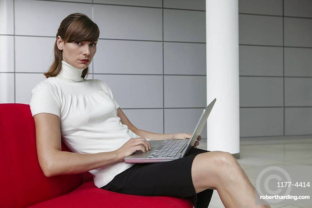 Portrait beautiful young businesswoman working at laptop in office lobby