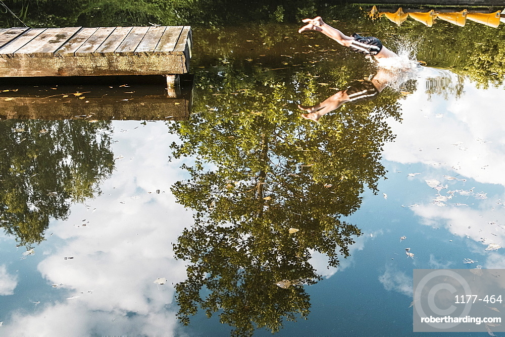Low section of boy diving into lake