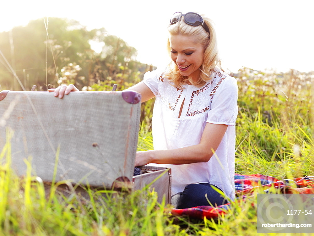 A woman sitting in the grass rummaging through an open suitcase