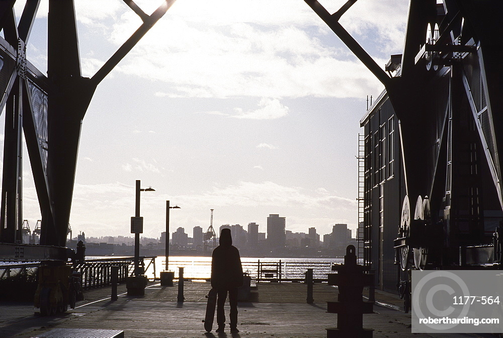 Full length rear view of man with skateboard looking at cityscape