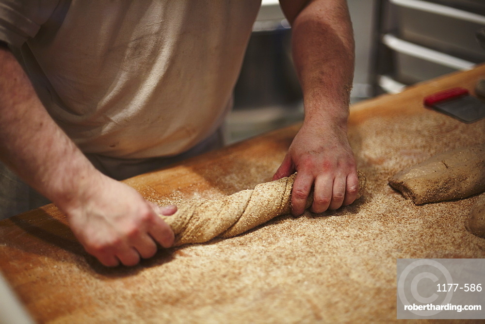 Mid section of man preparing bread at kitchen counter