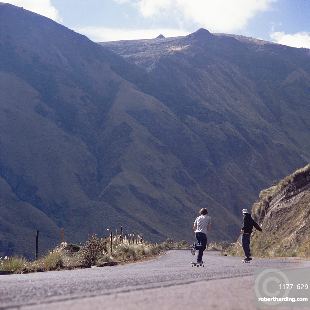 Two young men skateboarding down a steep road