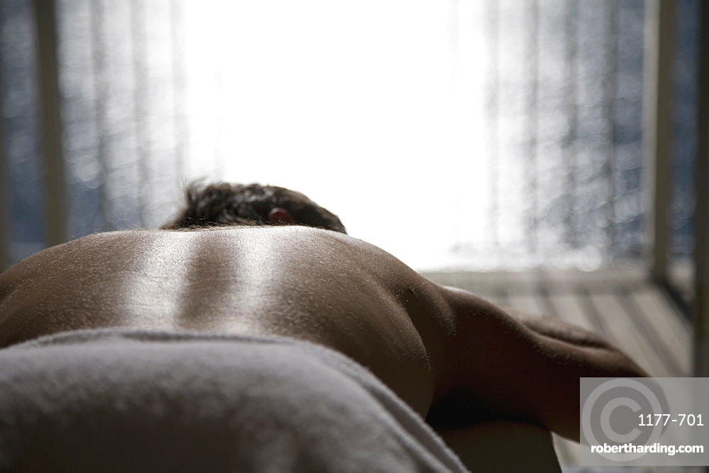 A man lying down on a massage table