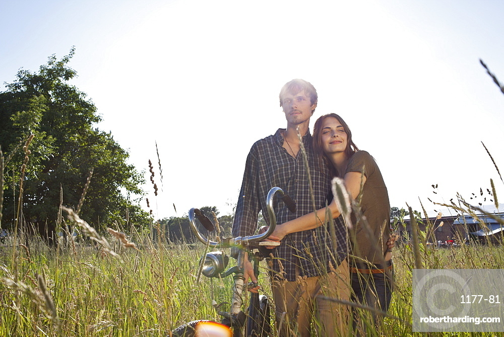 Couple with arms around each other walk through field with bike