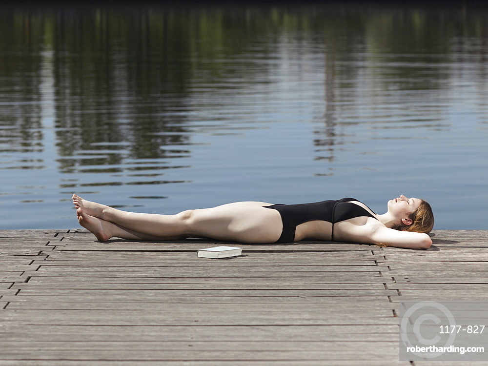 A woman in a swimsuit lying on a jetty