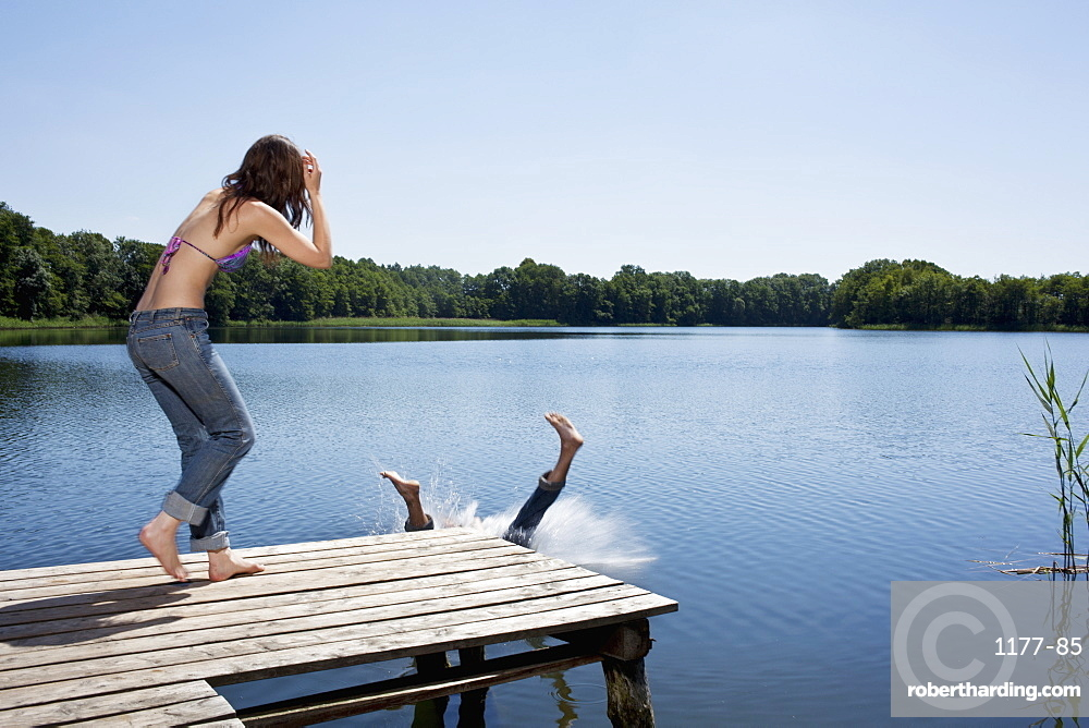 Guy splashes into water from jetty as girl watches