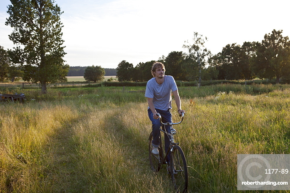 Guy cycles through secluded field on bike