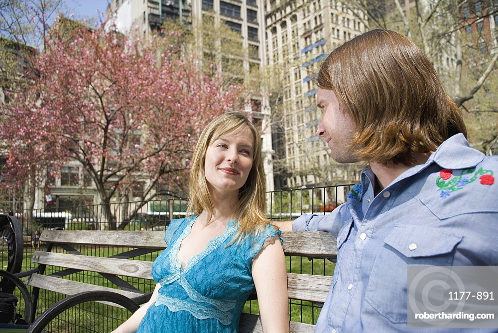 A young couple sitting on a park bench together, central park, new york city