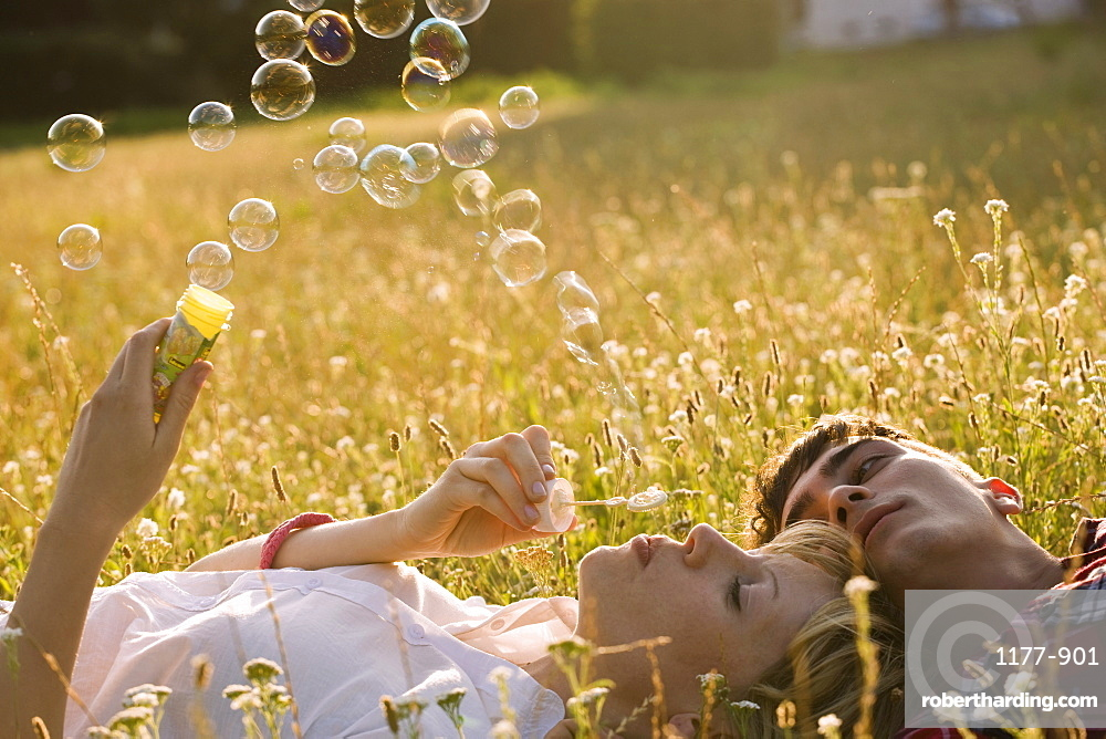 A young couple in a field blowing bubbles
