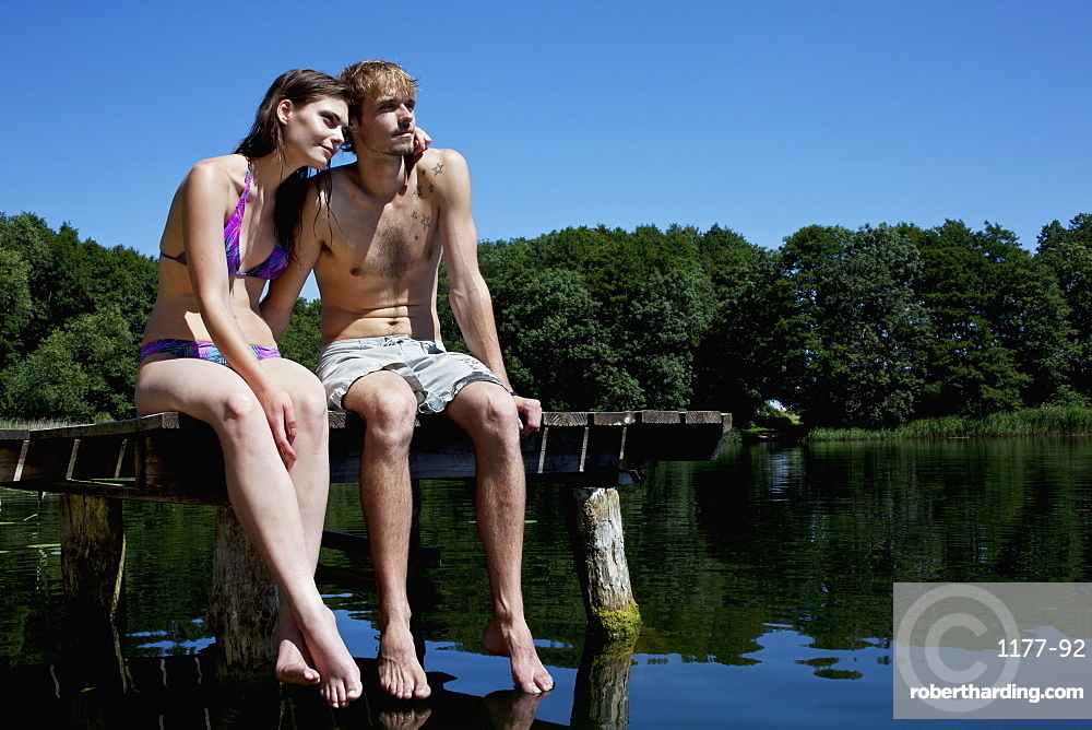 Couple sitting on edge of jetty by lake