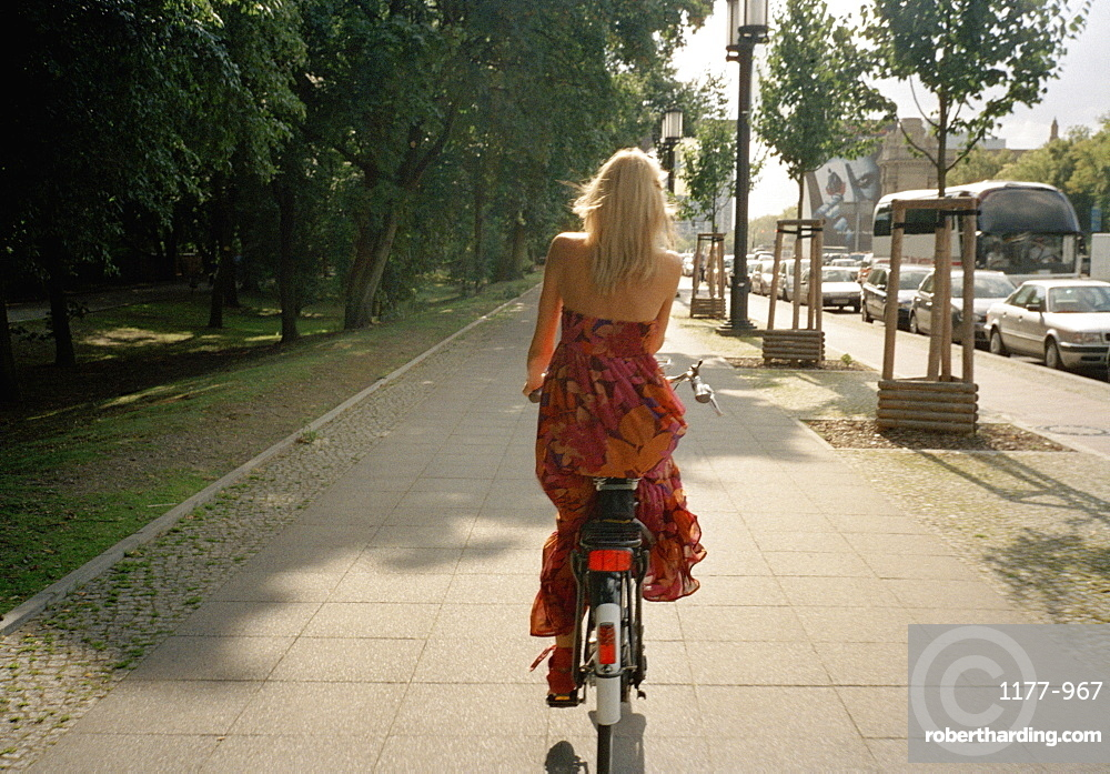 Rear view of a woman riding a bicycle on a footpath