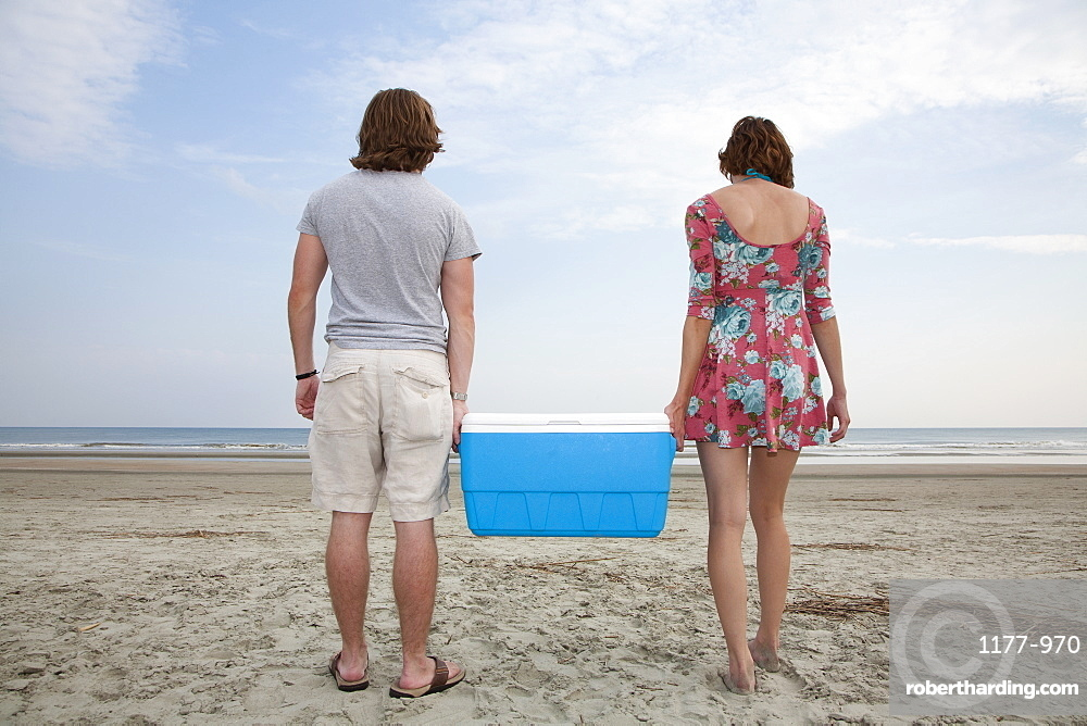 A young couple carrying a cooler together on the beach